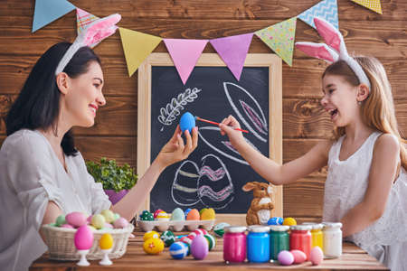 traditional: Mother and her daughter painting eggs. Happy family preparing for Easter. Cute little child girl wearing bunny ears.