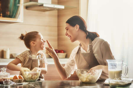Gelukkig liefdevolle familie bereiden bakkerij samen. Moeder en kind dochter meisje koken koekjes en plezier in de keuken. Huisgemaakte gerechten en weinig helper.