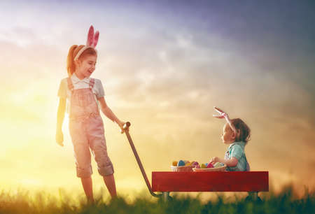 Two cute little children wear bunny ears and have Easter eggs. Girl carries her baby sister in kids wheel barrow in the rays of the setting sun. Stock Photo
