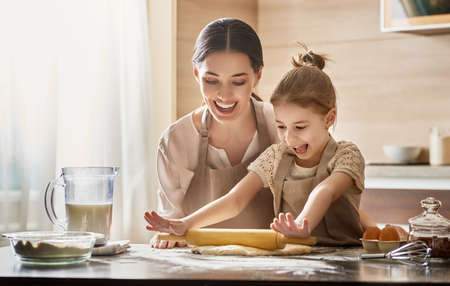 Happy loving family are preparing bakery together. Mother and child daughter girl are cooking cookies and having fun in the kitchen. Homemade food and little helper. Stok Fotoğraf - 74643127