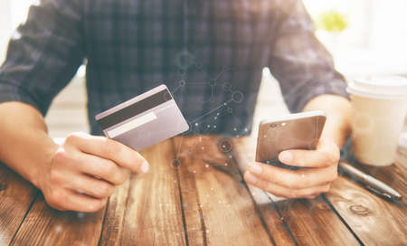 Man is holding credit card and using smartphone. Online shopping concept. Close up.