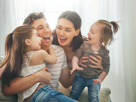 Happy fathers day! Two children daughters with mother congratulate daddy. Mum, dad and girls laughing and hugging. Family holiday and togetherness. Stock fotó