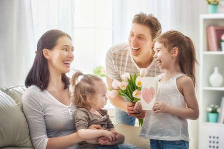 Gelukkige Moederdag! Twee kinderen dochters met papa feliciteren moeder en geef haar een kaartjes en bloemen tulpen. Mum en meisjes glimlachen en knuffelen. Vakantie met het gezin en saamhorigheid.