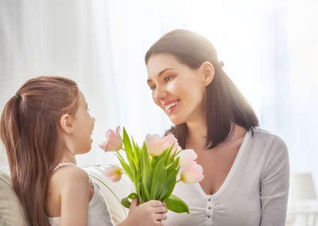 Happy mothers day! Child daughter congratulates mom and gives her flowers tulips. Mum and girl smiling and hugging. Family holiday and togetherness.