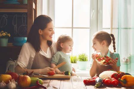 Gezond voedsel thuis. Gelukkig gezin in de keuken. Moeder en kinderen dochters bereiden de groenten en fruit.