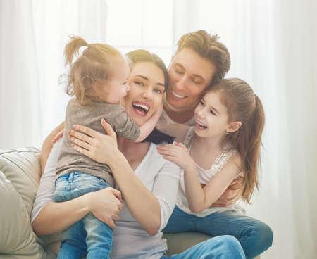 해피 어머니의 날! 아버지와 두 아이의 딸은 엄마를 축하드립니다. 엄마, 아빠와 웃는 여자와 포옹. 가족 휴가와 공생. 스톡 콘텐츠