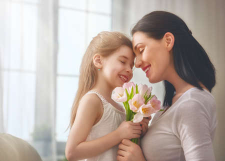 Happy mother's day! Child daughter congratulates mom and gives her flowers tulips. Mum and girl smiling and hugging. Family holiday and togetherness. Stock Photo