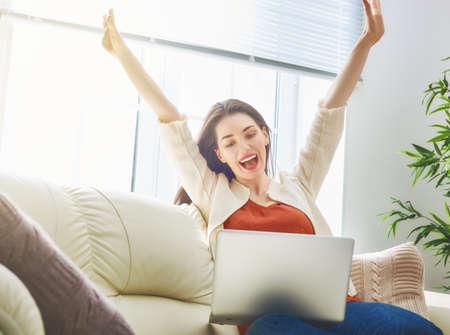 Gelukkig mooie vrouw kijken naar video's of genieten van entertainment content op een laptop zittend op de bank in het huis. Stockfoto