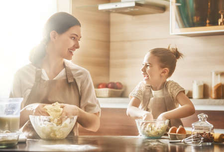 massage enfant: Bonne famille aimante préparent la boulangerie ensemble. Mère et enfant fille fille cuisinent biscuits et avoir du plaisir dans la cuisine. Cuisine maison et petite aide.