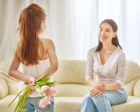 幸せな母の日!子娘はお母さんを祝うし、彼女の花チューリップを与えます。ママと女の子笑顔とハグします。家族の休日と一体感。 写真素材