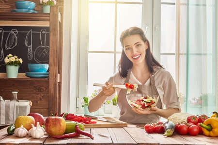 table: Healthy food at home. Happy woman is preparing the vegetables and fruit in the kitchen. Stock Photo