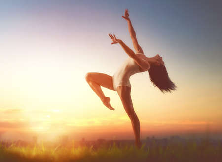 Young beautiful woman is dancing on sunset background outdoors. Concept of freedom and unity with nature. Stock Photo
