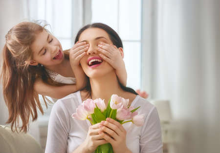 Happy mother's day! Child daughter congratulates mom and gives her flowers tulips. Mum and girl smiling and hugging. Family holiday and togetherness. Foto de archivo