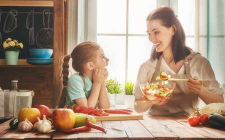 家庭での健康食品。台所での幸せな家族。母と子の娘は、野菜や果物を準備しています。