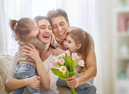 Happy mothers day! Two children daughters with dad congratulate mom and give her flowers tulips. Mum and girls smiling and hugging. Family holiday and togetherness.