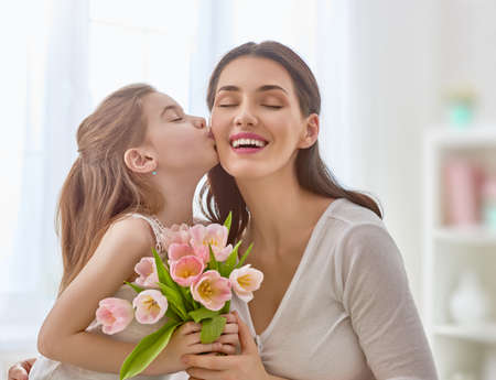 Happy mother's day! Child daughter congratulates mom and gives her flowers tulips. Mum and girl smiling and hugging. Family holiday and togetherness. Standard-Bild