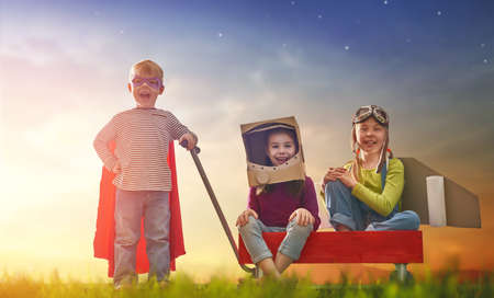dressed: Children in astronaut, pilot and super hero costumes are playing and dreaming. Portrait of funny kids on nature. Family friends games outdoors. Stock Photo