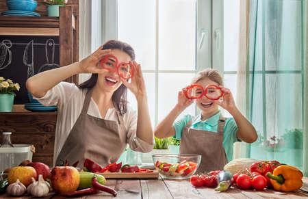 niños cocinando: La comida sana en casa. Familia feliz en la cocina. Madre e hija hijo están preparando las verduras y frutas.