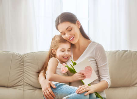Happy mother's day! Child daughter congratulates mom and gives her flowers tulips and postcard. Mum and girl smiling and hugging. Family holiday and togetherness. Stockfoto