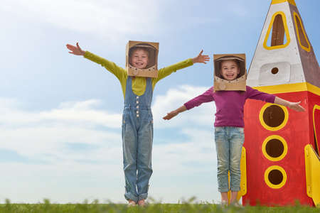Children in astronauts costumes with toy rocket playing and dreaming of becoming a spacemen. Portrait of funny kids on nature. Family friends games outdoors.