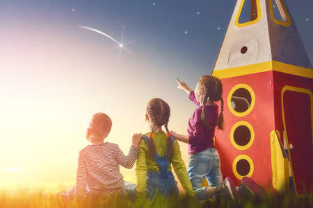 Children playing with toy rocket and dreaming of becoming a spacemen. Portrait of funny kids looking at the sky. Family friends games outdoors. Boy and girls make a wish by seeing a shooting star. Archivio Fotografico