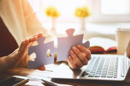 여자는 몇 가지 퍼즐 조각을 연결하려고합니다. 협회 및 연결의 상징입니다. 비즈니스 전략의 개념입니다.