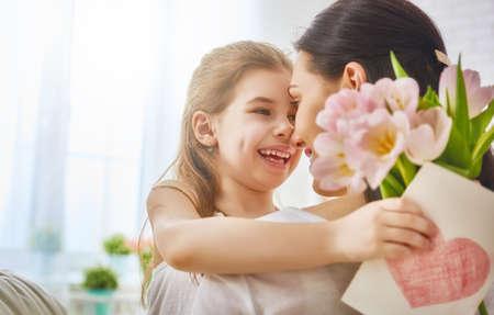 해피 어머니의 날! 어린 딸은 엄마를 축하하고 그녀의 튤립 꽃과 엽서를 제공합니다. 엄마와 소녀 미소와 포옹. 가족 휴가와 공생. 스톡 콘텐츠
