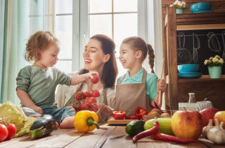 Healthy food at home. Happy family in the kitchen. Mother and children daughters are preparing the vegetables and fruit.