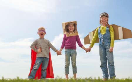 Los niños en astronauta, piloto y trajes de superhéroes están riendo, jugando y soñando. Retrato de niños divertidos sobre la naturaleza. Amigos de la familia de juegos al aire libre. Foto de archivo - 75183036