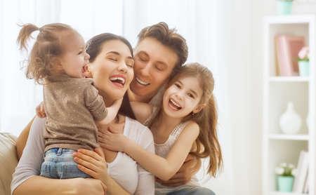 mom dad: ¡Feliz día de la madre! Dos hijas Niños con el padre felicitan madre. Madre, padre y niñas riendo y abrazos. vacaciones en familia y la unión. Foto de archivo