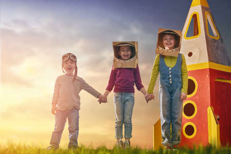 Children in astronauts costumes with toy rocket playing and dreaming of becoming a spacemen. Portrait of funny kids on a background of sunset star sky on nature. Family friends games outdoors.