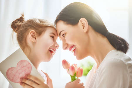 Happy mother's day! Child daughter congratulates mom and gives her flowers tulips and postcard. Mum and girl smiling and hugging. Family holiday and togetherness. Stok Fotoğraf