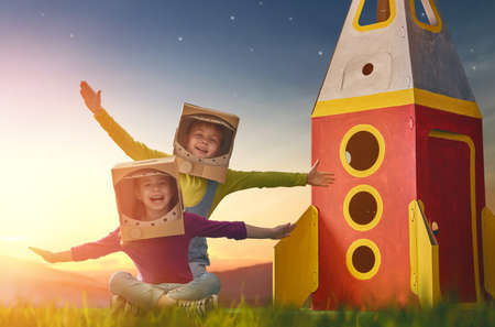 Children in astronauts costumes with toy rocket playing and dreaming of becoming a spacemen. Portrait of funny kids on a background of sunset star sky on nature. Family friends games outdoors. Stock fotó - 75653784