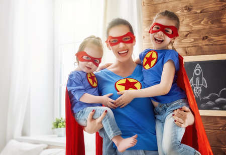 Mãe e seus filhos brincando juntos. Meninas e mãe em trajes de super-heróis. Mãe e filhos se divertindo, sorrindo e abraçando. férias em família e união.
