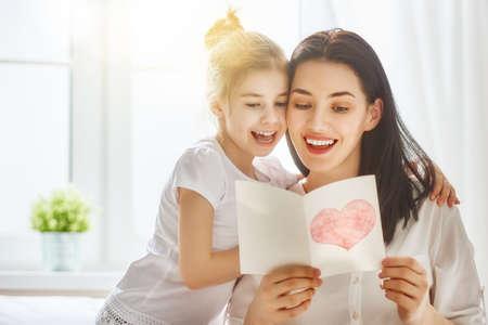 Gelukkige Moederdag! Child dochter feliciteert moeder en geeft haar briefkaart. Mama en meisje lachend en knuffelen. Vakantie met het gezin en saamhorigheid. Stockfoto