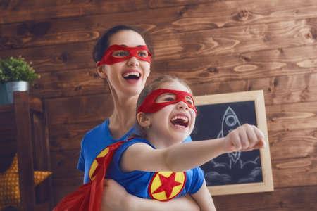 M�e e filho tocando juntos. Menina e mam� no traje do super-her�i. Mum e mi�do se divertindo, sorrindo e se abra�ando. f�rias em fam�lia e uni�o. Imagens