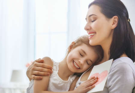 Happy mothers day! Child daughter congratulates mom and gives her postcard. Mum and girl smiling and hugging. Family holiday and togetherness.