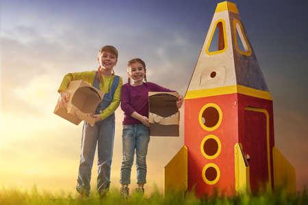 Los niños en trajes de los astronautas con cohete de juguete jugando y soñando con ser astronautas. Retrato de niños divertidos sobre un fondo de cielo estrellado puesta de sol en la naturaleza. Amigos de la familia de juegos al aire libre. Foto de archivo - 75653851