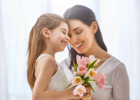 happy mom: Happy mothers day! Child daughter congratulates mom and gives her flowers tulips. Mum and girl smiling and hugging. Family holiday and togetherness.
