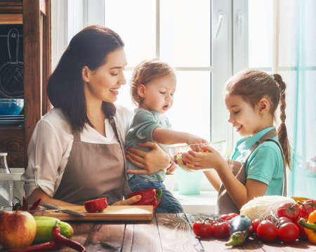 a little dinner: Healthy food at home. Happy family in the kitchen. Mother and children daughters are preparing the vegetables and fruit.