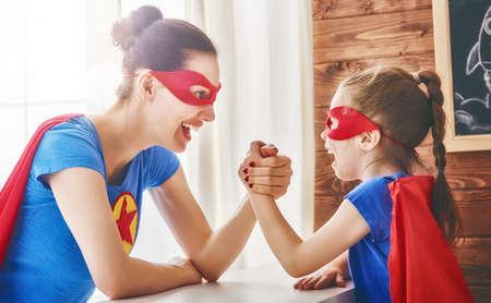 어머니와 그녀의 아이가 함께 연주. 슈퍼 히어로 의상 소녀와 엄마. 엄마와 아이, 재미 미소와 포옹. 가족 휴가와 공생.