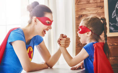 Mother and her child playing together. Girl and mom in Superhero costume. Mum and kid having fun, smiling and hugging. Family holiday and togetherness. Stock fotó - 76108290
