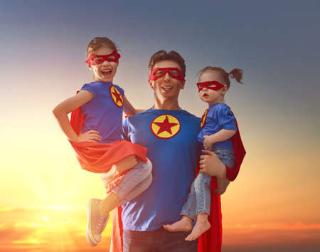 幸せな愛情のある家族。お父さんと娘さんは屋外で遊んでいます。パパとスーパー ヒーローの衣装で彼の子供の女の子。父の日の概念。