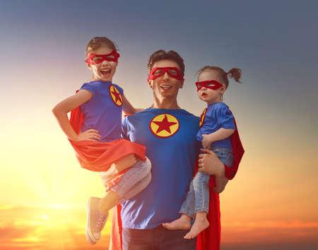 Glückliche liebevolle Familie. Dad und seine Töchter spielen im Freien. Papa und seine Kinder Mädchen in einem Superhelden Kostüme. Konzept des Vatertags. Standard-Bild - 76108301