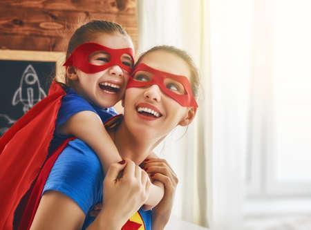 Mutter und ihr Kind zusammen zu spielen. Mädchen und Mutter in Superheld-Kostüme. Mama und Kind Spaß, lächelnd und umarmt. Familienurlaub und Zusammengehörigkeit.