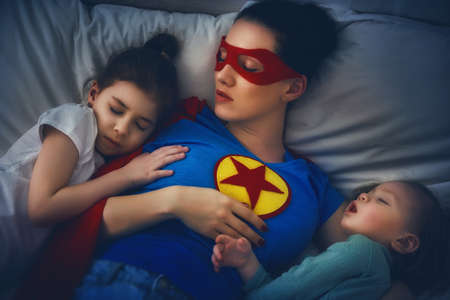 Adorable little children girls are napping in the bed with their mom. Quiet sleep under the protection of the mother superhero. Stock fotó - 76109297