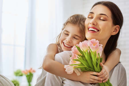 Happy mother's day! Child daughter congratulates mom and gives her flowers tulips. Mum and girl smiling and hugging. Family holiday and togetherness. 免版税图像