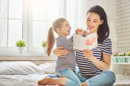 해피 어머니의 날! 어린 딸은 엄마를 축하하고 그녀의 엽서를 제공합니다. 엄마와 소녀 미소와 포옹. 가족 휴가와 공생. 스톡 콘텐츠