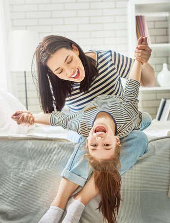 Gelukkige Moederdag! Moeder en haar dochter kind meisje spelen en glimlachend. Vakantie met het gezin en saamhorigheid.