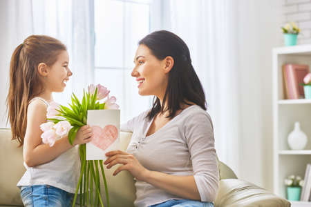 Happy mother's day! Child daughter congratulates mom and gives her flowers tulips and postcard. Mum and girl smiling. Family holiday and togetherness.